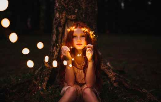 A white kid with long red hair, a string of lights around her head, sitting in front of a tree trunk at night, holding the lights in her hand, looking past the camera. Photo by Matheus Bertelli on Pexels.com