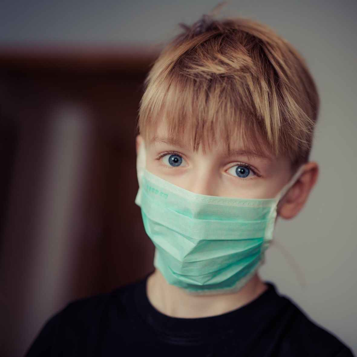 Kid with a medical mask on looking into the camera. Photo by Janko Ferlic on Pexels.com