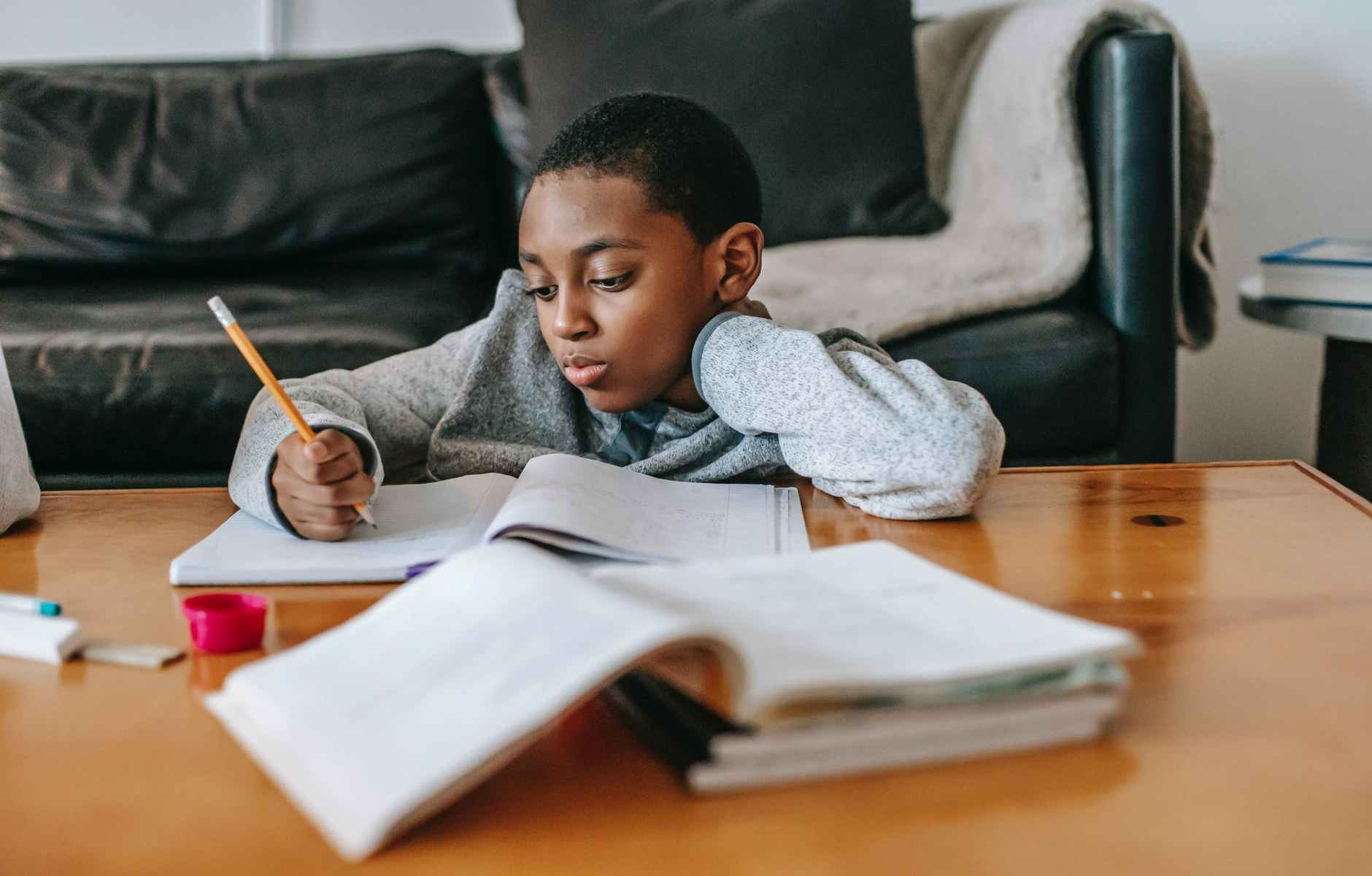 frustrated black kid with grey sweatshirt doing homework