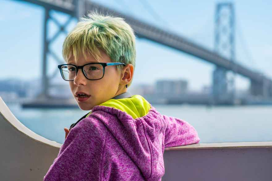 White boy with blonde and green hair and freckles, with glasses on leaning on a building, looking past the camera with mouth slightly open. Wearing a purple hoodie with neon green on the inside of it. A bridge by a city is in the background of the image.