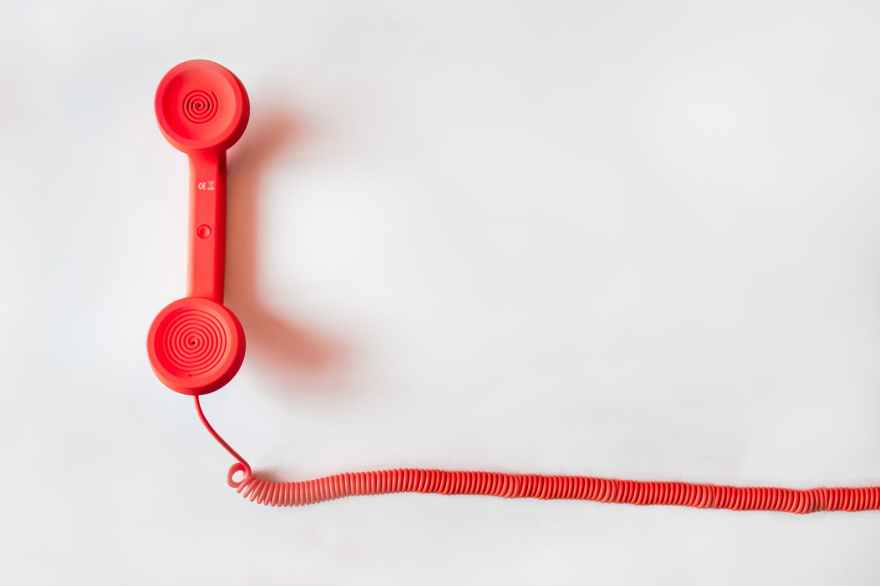 Red landline phone with earphone point up laying on a white background.