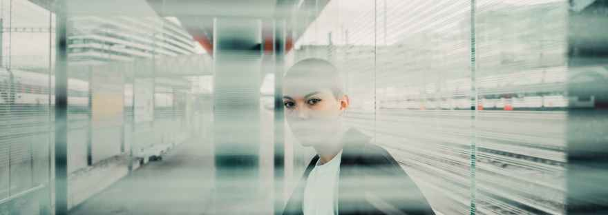 Woman with shaved head sitting in a hallway office behind a glass window with her face obscured by blinds in that are in the foreground of the image.