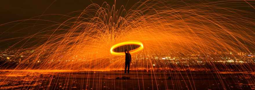 Person standing far away with a circle of life above their head and orange sparks flying like a fountain off of the circle.