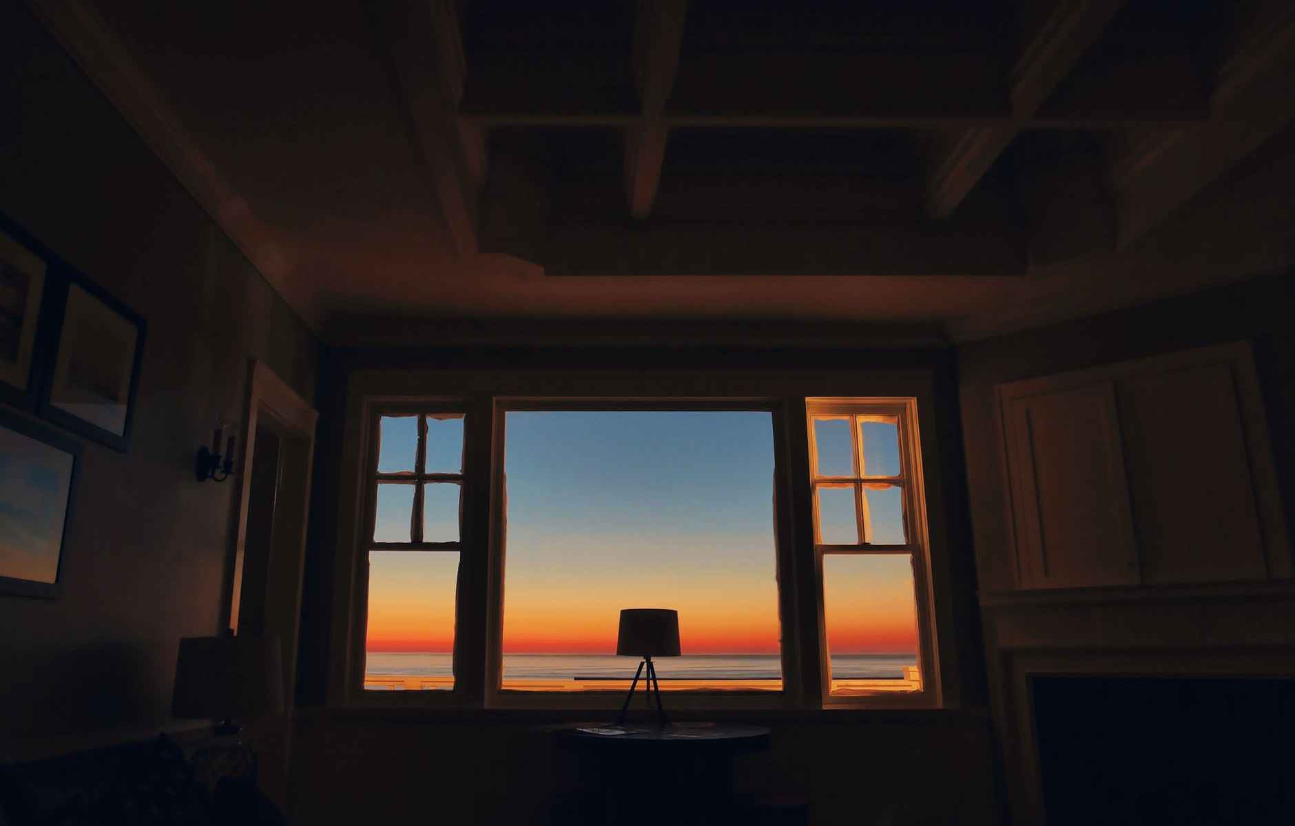 inside house looking out a window with a sunset painted on the wall
