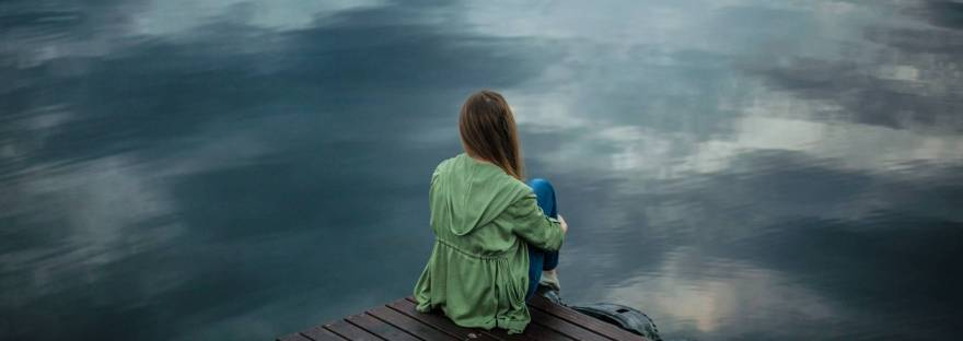 Person with green jacket and jeans sitting on a dock with long hair, face looking away from camera.