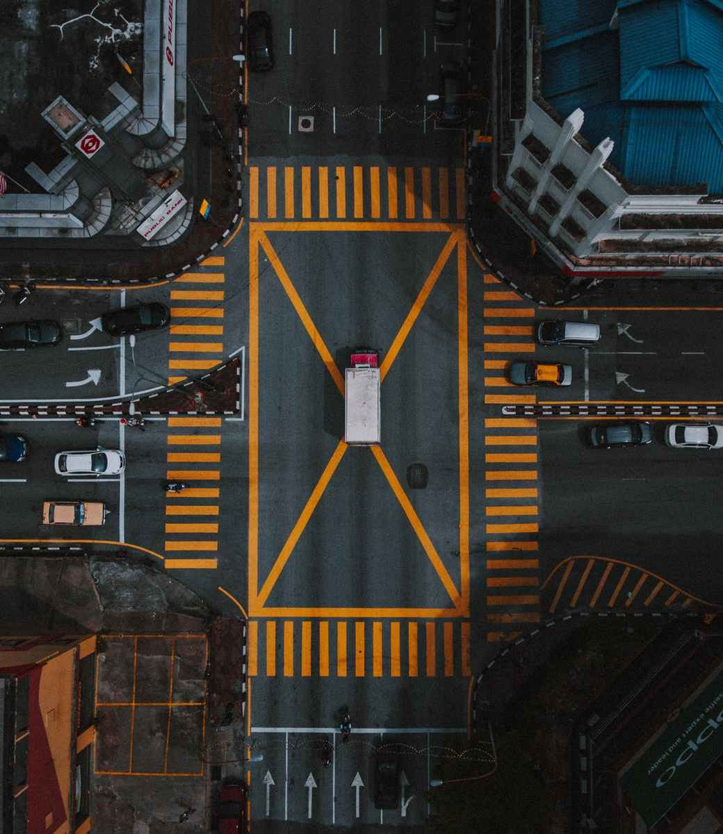 aerial photography of cars on the road. A truck in the middle of a big yellow X above a busy intersection.
