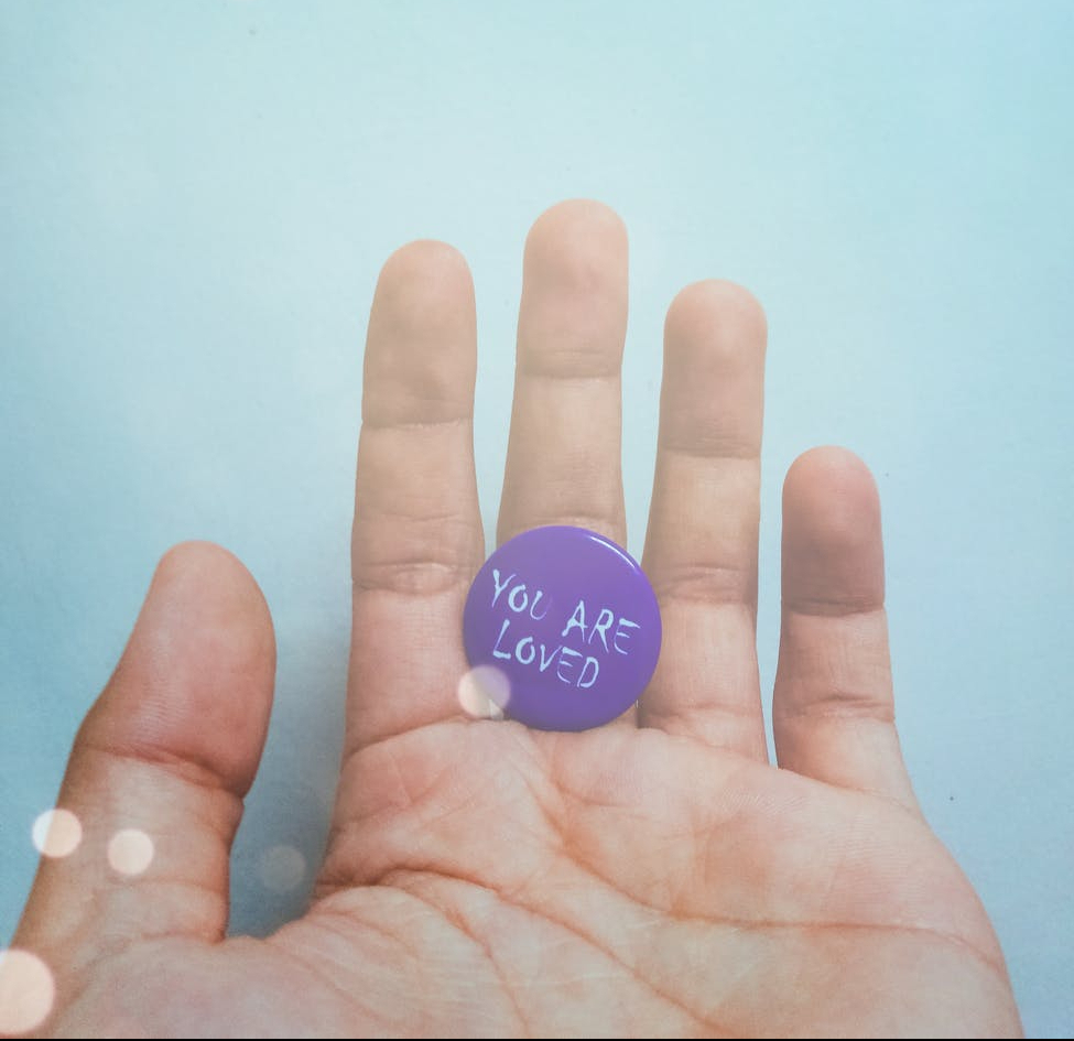Picture of palm of someone's hand with a blue background and light spots. Hand has a button in it that's painted purple and says you are loved in white letters.