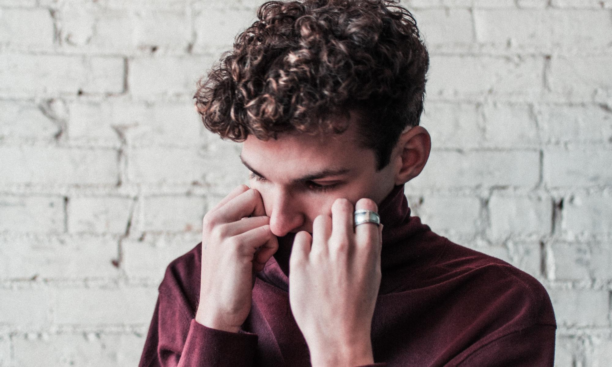 White person with brown curly hair covering up his mouth with his red shirt collar.
