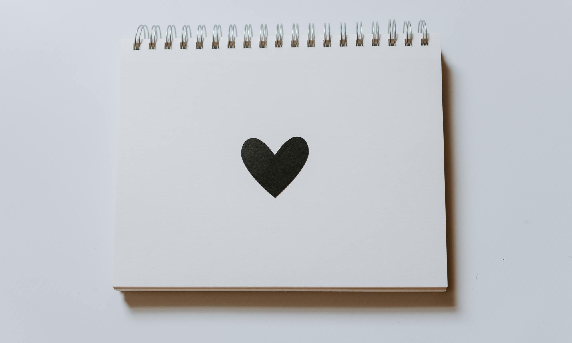 Notebook with black heart on the front of it
