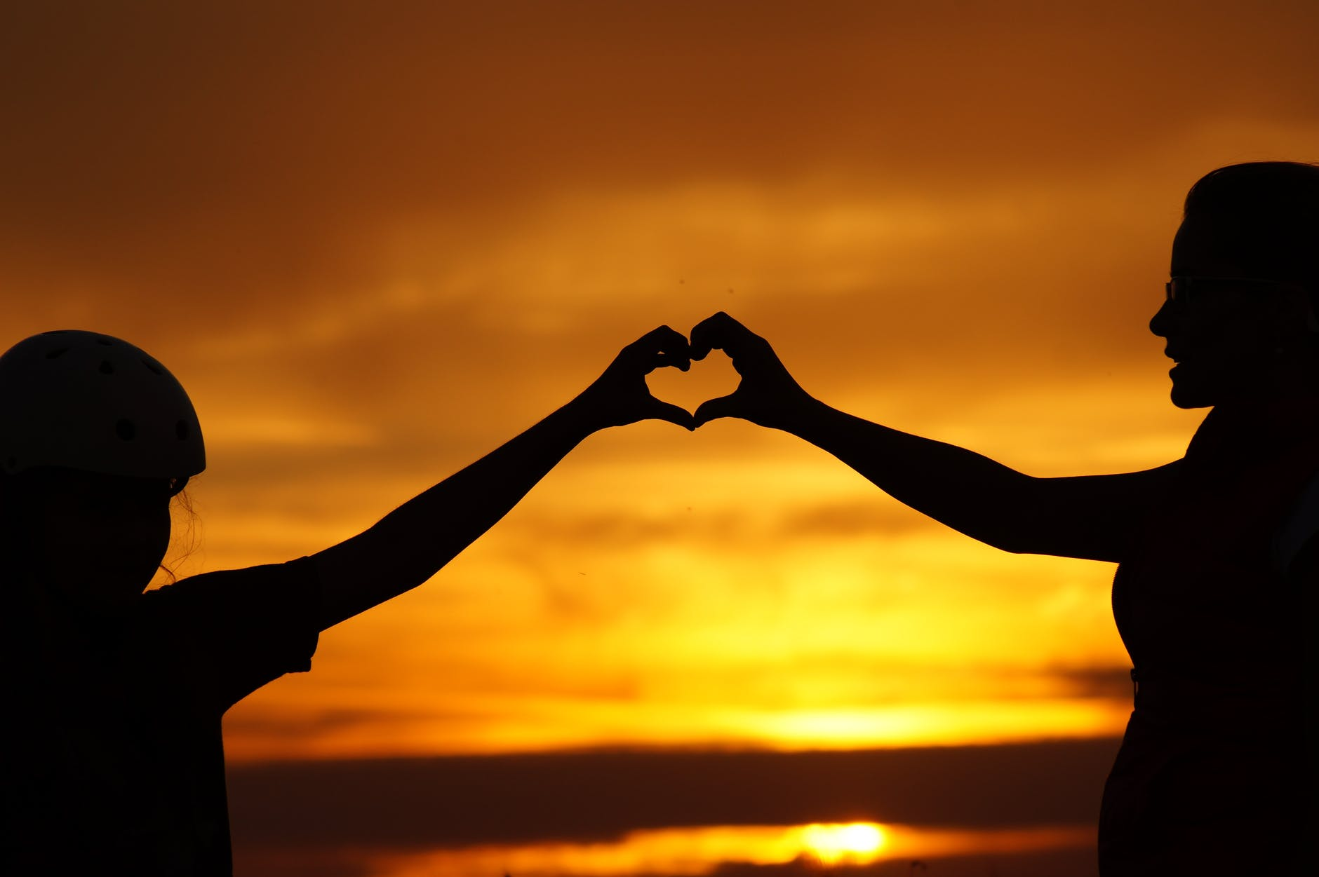 silhouette of child hands touching a parent's hands against sunset sky forming a heart