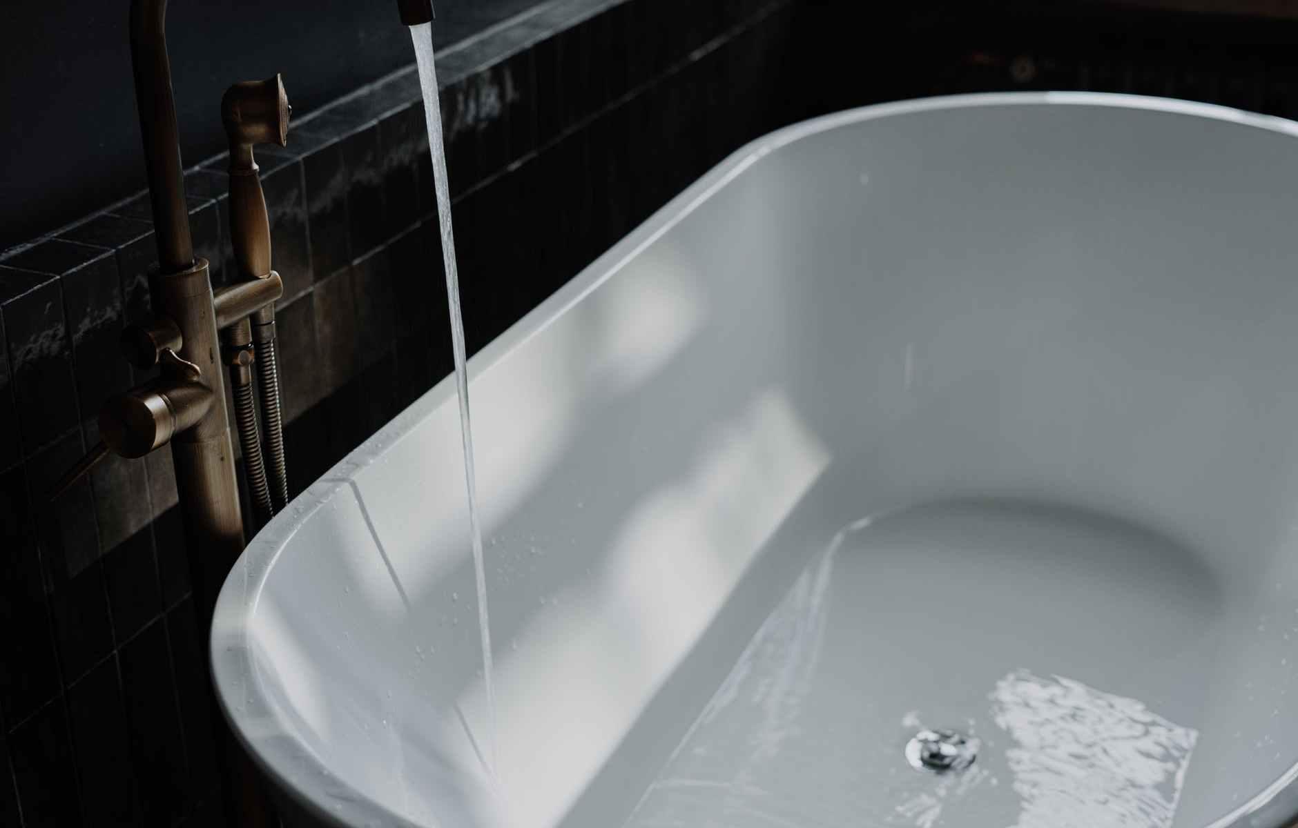 white ceramic bathtub with running water