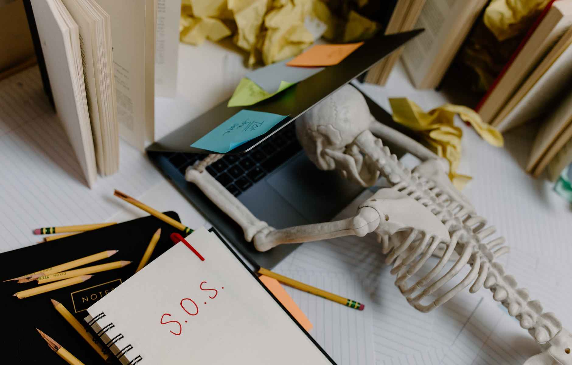 skeleton with head on a laptop with sticky notes and a notebook that says S O S in red ink.
